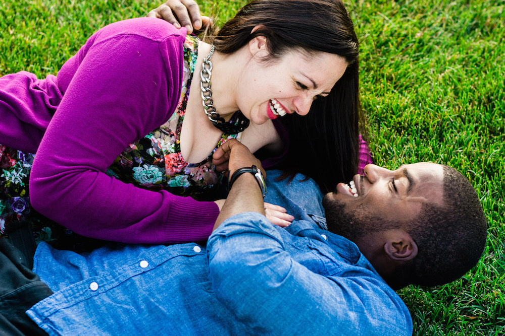 cute-interracial-couple-laughing-laying-in-grass-engagement-photos-nj-wedding-photographer-eagle-rock-reservation-west-orange
