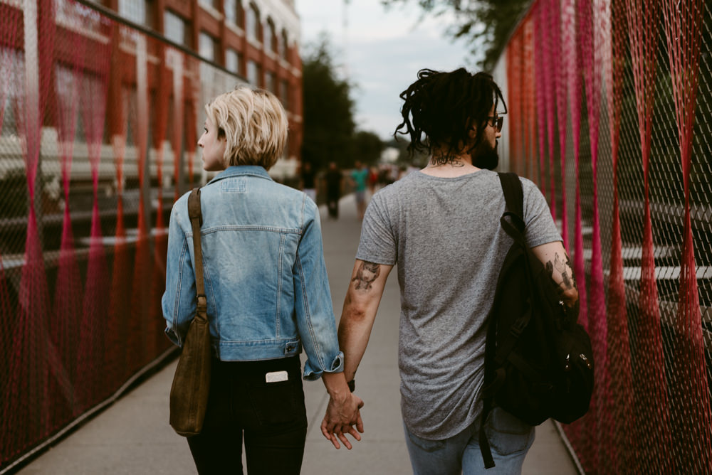 holding-hands-walking-bridge-hot-couple-madewell-forever-21-urban-outfitters-ponce-city-market-beltline-kelly-baysinger-adam-tuminaro-atlanta-georgia-wedding-photographer
