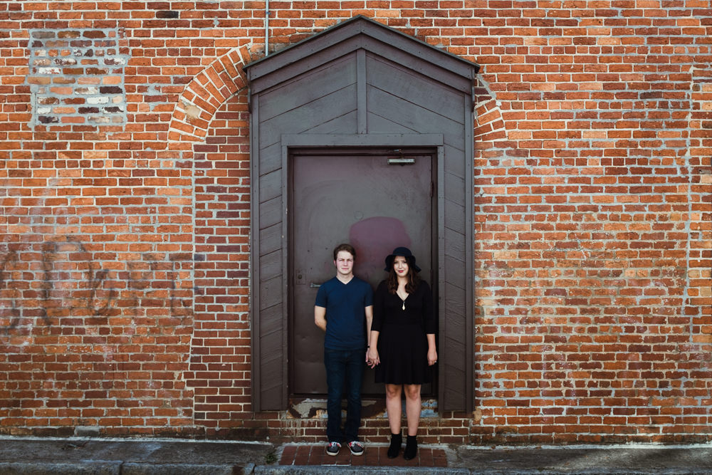 couple-holding-hands-brick-wall-emily-steve-cole-marietta-square-atlanta-georgia-wedding-photographer