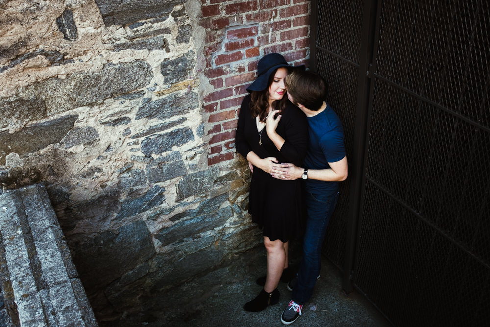 cute-couple-corner-brick-wall-iron-gate-emily-steve-cole-marietta-square-atlanta-georgia-wedding-photographer