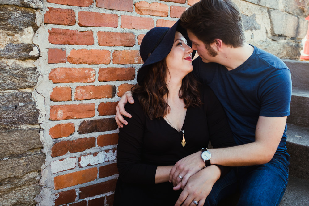 cute-couple-cuddling-brick-wall-stairs-emily-steve-cole-marietta-square-atlanta-georgia-wedding-photographer