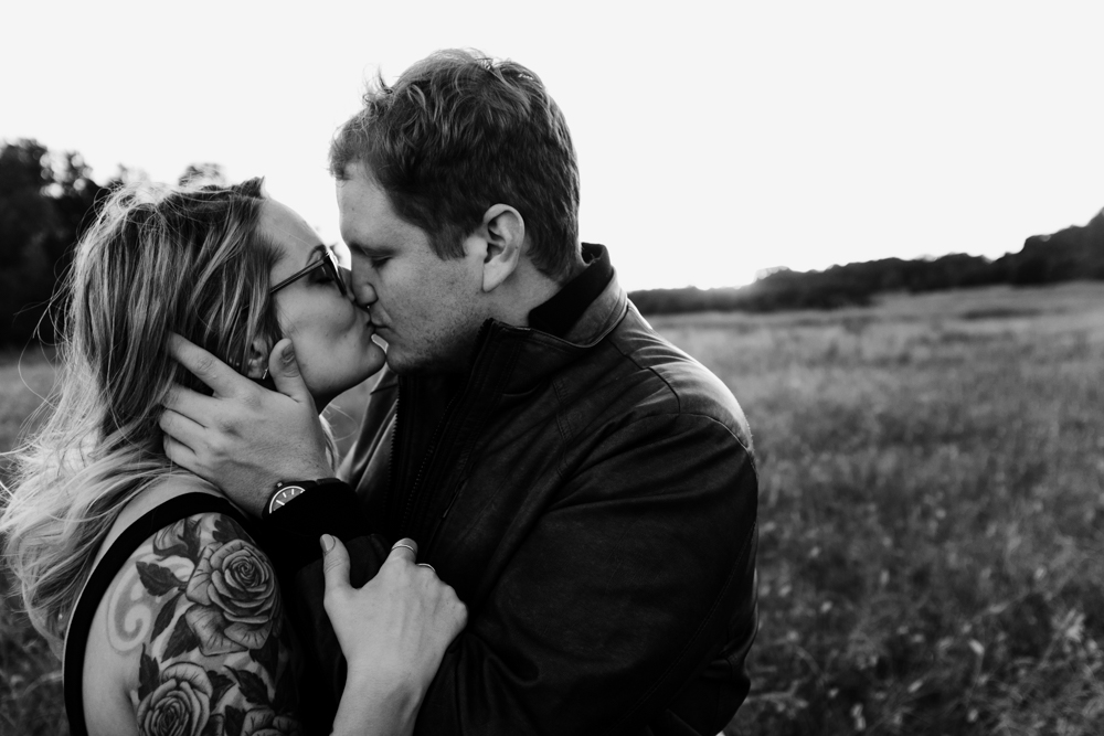 cute-couple-kiss-field-sunset-black-white-forever-21-river-west-arabia-mountain-atlanta-georgia-wedding-photographer
