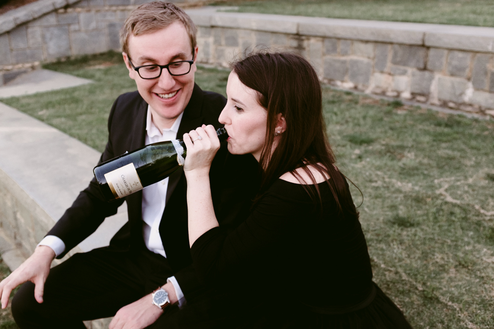 couple-champagne-drink-funny-maggie-wolicki-lang-burghardt-engagement-photos-atlanta-wedding-old-fourth-ward-park