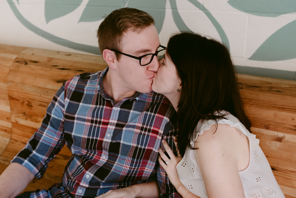 cute-couple-kiss-bench-maggie-wolicki-lang-burghardt-engagement-photos-atlanta-wedding-ponce-city-market