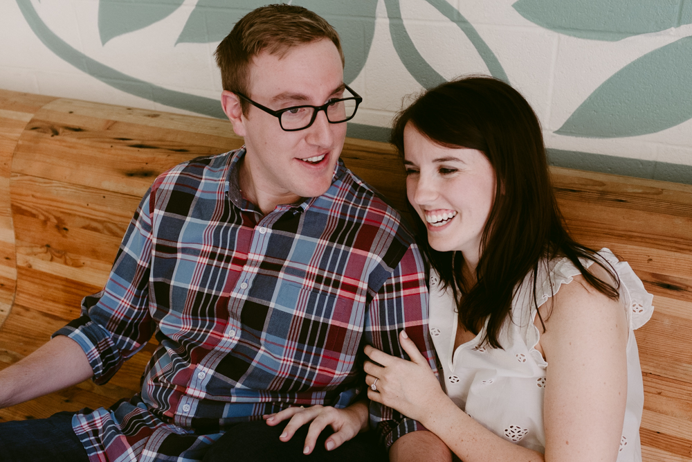 cute-couple-laugh-bench-maggie-wolicki-lang-burghardt-engagement-photos-atlanta-wedding-ponce-city-market