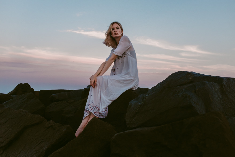 beautiful-pastel-sunset-pretty-model-sitting-rocks-sky-ashley-jensen-nj-wedding-photographer-asbury-park-ocean-grove-2
