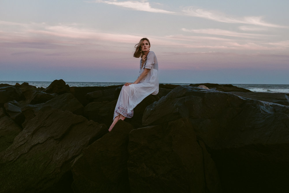 beautiful-pastel-sunset-pretty-model-sitting-rocks-sky-ashley-jensen-nj-wedding-photographer-asbury-park-ocean-grove