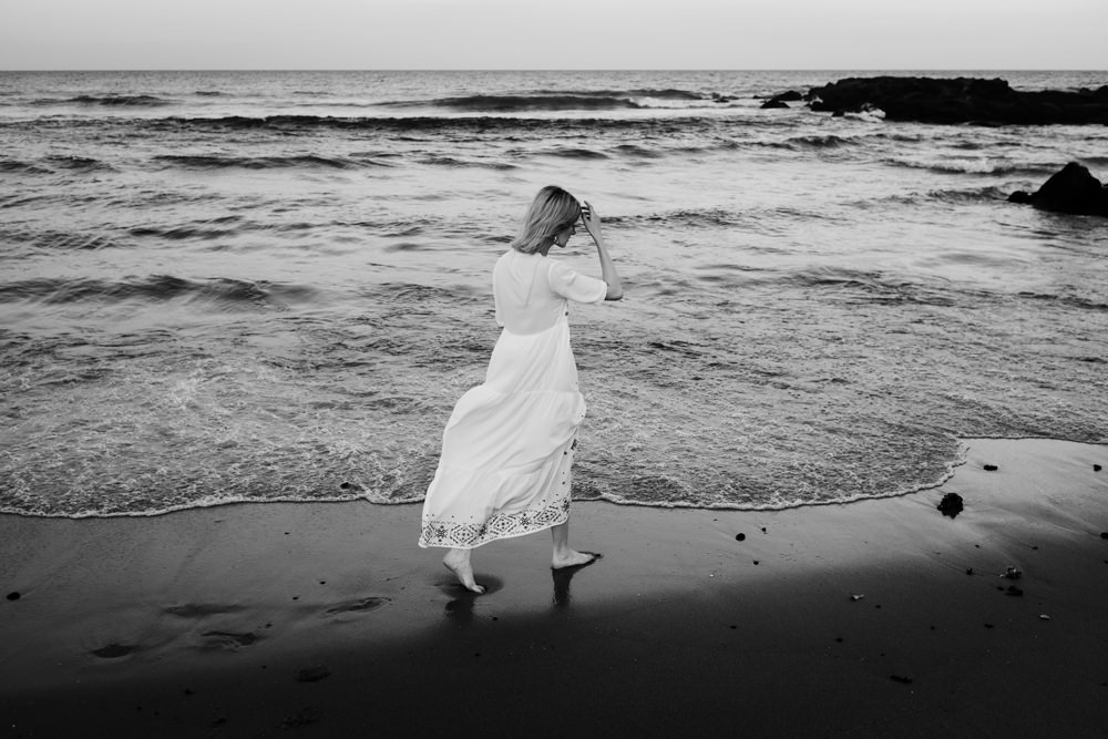 girl-walking-along-beach-ashley-jensen-nj-wedding-photographer-asbury-park-ocean-grove