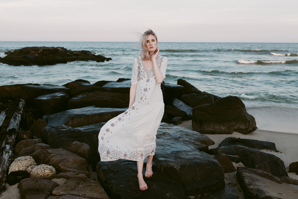 pretty-blonde-model-beach-rocks-jetty-ocean-waves-ashley-jensen-nj-wedding-photographer-asbury-park-ocean-grove